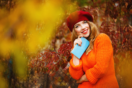 seeks: Lovely girl in a beret and a sweater walking in autumn park, holding a notebook. The poet seeks inspiration. Girl enjoying fresh air. The girl white smile. The concept of modern youth fashion.