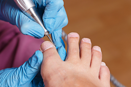 chiropodist: Master pedicure shapes the nails and cuticles closeup. Hardware manicure. Concept body care.