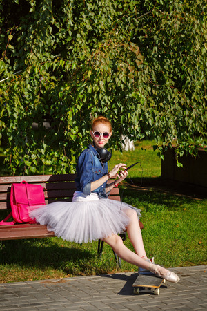 communicates: Girl listening to music on headphones. Funny hipster ballerina sitting on a bench. A girl wearing a tutu, ballet shoes and sneakers, sunglasses. Skateboard. She communicates in social networks. The concept of youth fashion.