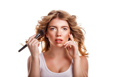 visagist: Beautiful young girl with curly hair straightens makeup brush makeup. Cosmetic skin care. Visagist. Beauty salon. Stock Photo