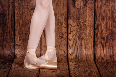 pas: Fifth position in classical ballet. Slender legs of a ballerina in pointe shoes. Photo closeup. Ballet pas.