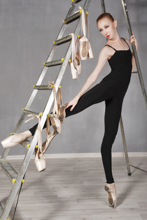 ballerina tights: Slim ballerina in black tights and pointe standing next to a ladder.