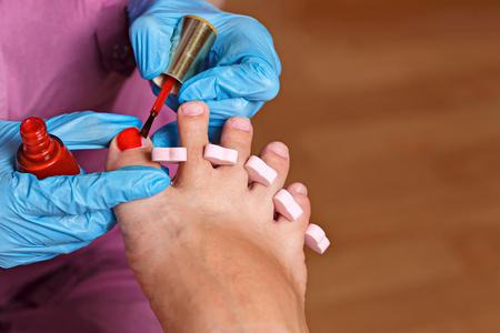 chiropody: Master chiropody applying gel nail polish.