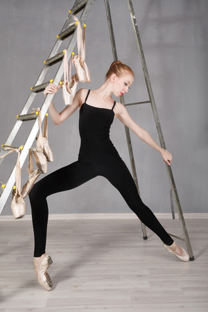 ballerina tights: Slender ballerina in black tights and pointe shoes standing next to stepladder. Stock Photo