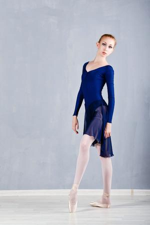 en pointe: Young slim ballerina in a blue dress dancing. Graceful girl. Performance. Classical Ballet. Stock Photo
