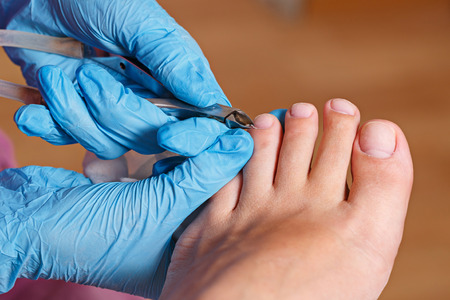 Master chiropody removes the cuticle.