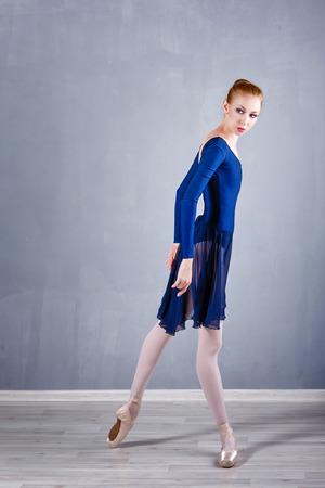 ballerina shoes: Young graceful ballerina in a blue dress dancing.