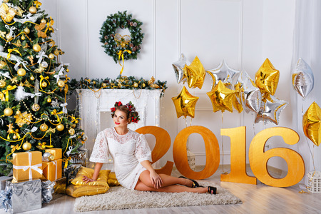woman hairstyle: A girl sitting on the carpet next to the Christmas tree and presents. Stock Photo