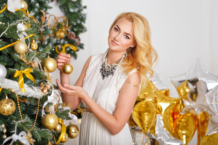 decorates: Young girl decorates the Christmas tree. Stock Photo