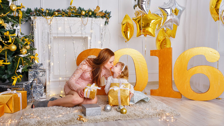 adorable child: Family celebration of the New Year 2016. The mother kisses daughter near a Christmas tree. Giving gifts. Holiday and fun.