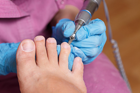 chiropody: Master chiropody shapes the nails and cuticles close up. Hardware manicure. Concept body care. Stock Photo