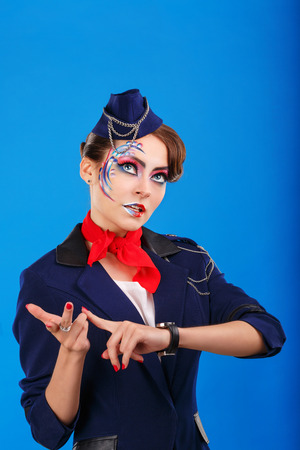considers: Stewardess with face art considers fingers. Young attractive girl in a blue suit flight attendants. Air transportation. Service.