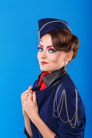 air freight: Stewardess with face art corrects jacket. Young attractive girl in a blue suit flight attendants. Air freight.