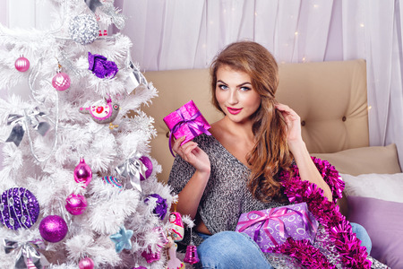 miracle tree: Girl sits on a sofa near the Christmas tree. New Year. Waiting for a miracle. Merry Christmas. Home comfort. Girl lays out gifts. Stock Photo