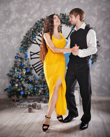 time sensitive: Couple dancing sensual dance. In the background, the clock shows five minutes to midnight. Christmas party. The concept of holiday and fun.