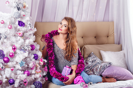 miracle tree: Girl sits on a couch near the Christmas tree. New Year. Waiting for a miracle. Merry Christmas. Home comfort. Girl lays out gifts. Model Posing.
