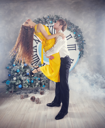 time sensitive: Couple dancing sensual dance. Man holds girl in his arms. In the background, the clock shows five minutes to midnight. Christmas party. The concept of holiday and fun. Stock Photo