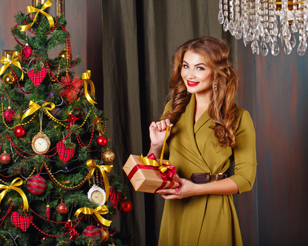 miracle tree: Girl unpacks gift. Christmas tree. New Year. Waiting for a miracle. Merry Christmas. Stock Photo
