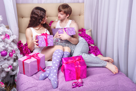 wife: Couple in love in bed. Husband and wife exchanged gifts. Christmas for Two. The concept of holiday and fun. Simple family happiness.