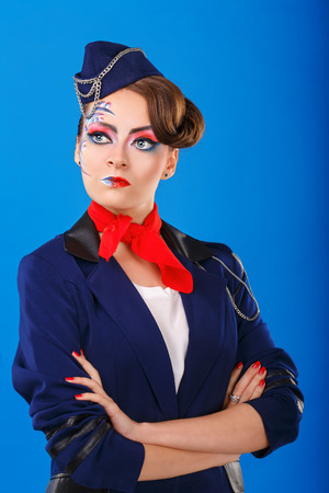 air freight: Stewardess with face art posing with folded arms. Young attractive girl in a blue suit flight attendants. Air freight. Service.
