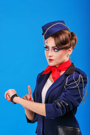air freight: Stewardess with face art shows to watch. Young attractive girl in a blue suit flight attendants. Air freight. Service. Stock Photo