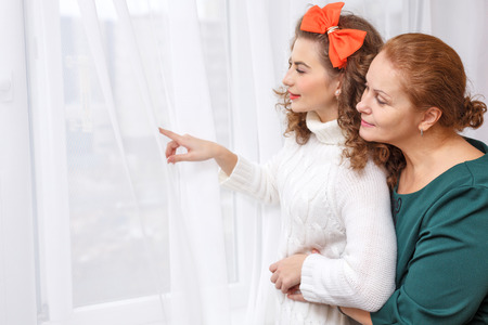 displays: Daughter of the window displays. Mother looks. Family hug and relationships. Home comfort. Stock Photo