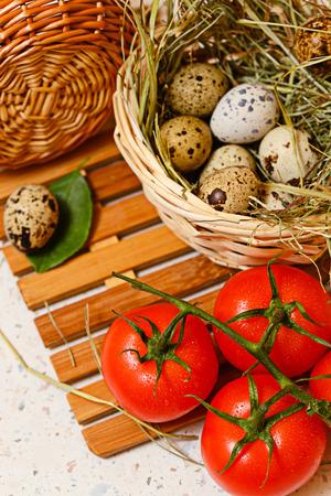 huevos codorniz: huevos de codorniz en la cesta. Un tomate.