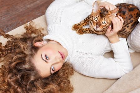 amigos abrazandose: La muchacha y el gato a casa de leopardo. confort en el hogar. Muchacha y un gato acostado en el sofá.