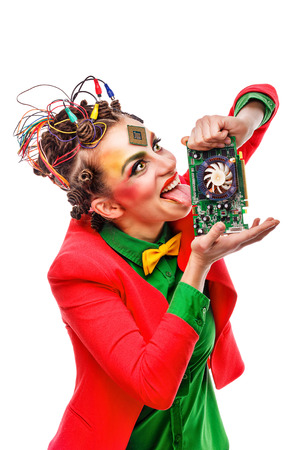 Girl geek licks graphics card. Crazy programmer. Creative make-up, hairstyle with wires and processor.
