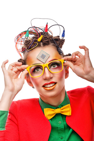 Girl geek corrects glasses. Crazy programmer. Creative make-up, hairstyle with wires and processor. Stock Photo