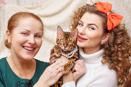 amigos abrazandose: Madre, hija y un gato. Abrazos con una mascota. Gato de Bengala. Gato en las cuentas.