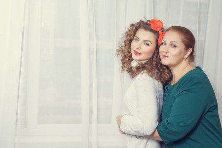 pre adult: Mother and daughter hugging. Toning. Family. Home comfort. Stock Photo