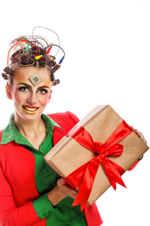 Girl geek holding a gift. Crazy programmer. Creative make-up, hairstyle with wires and processor. Stock Photo