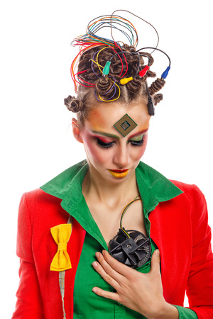 Girl geek corrects the cooler in place of the heart. Crazy programmer. Creative make-up, hairstyle with wires and processor. Stock Photo