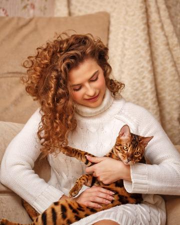 amigos abrazandose: Girl and leopard cat home. Home comfort. Girl hugging cat. Foto de archivo