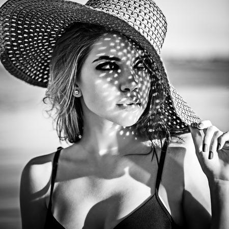 50671629 - Chica coqueteando en el sombrero. El concepto de vacaciones de  verano. Fotografía en blanco y negro Disparo en clave baja. a7e41708452