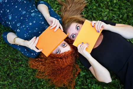 cute girl smiling: Young cheerful girlfriends lie on the lawn in the city park. Best friends. Lovely girl students hiding faces behind notebooks.