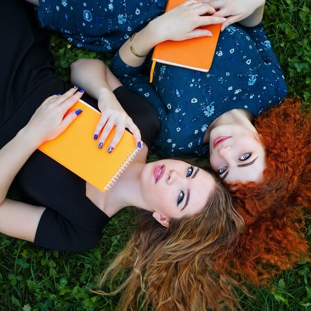 best friends girls: Young cheerful girlfriends lie side by side on the lawn in the city park. Best friends. Lovely girl student holding a notebook. Stock Photo