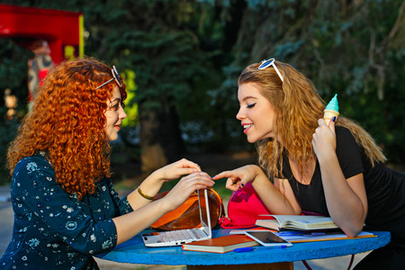 communicates: Best friends students in a city park. Girl communicates in social networks. Girl eating ice cream and watches the girlfriend. Education and recreation.