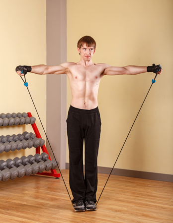 powerfully: Man sportsman doing rope climbs. Training in the sport club. Fitness. Stock Photo