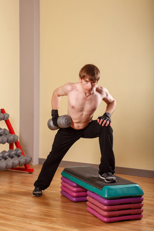 powerfully: Athletic build Man doing exercises with dumbbells. Training in the sport club. Fitness.