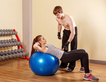 Entrenador personal ayudar a una niña aprender a presionar fitbar. Club de fitness. Programa de pérdida de peso. Salud y Belleza.
