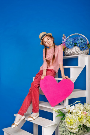 suspenso: muchacha adolescente linda que sostiene una tarjeta de San Valentín. Corazón de papel grande. Día de San Valentín. Foto de archivo