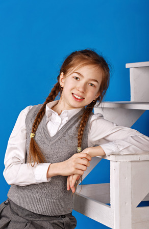 emotion faces: Cute teen girl in school uniform. The girl smiles. Stock Photo