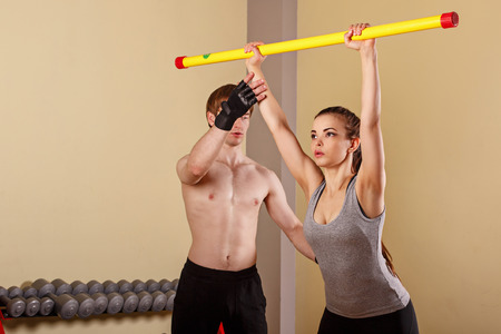 supple: Personal trainer helping girl learn exercise with fitbar. Fitness club. Weight loss program. Sport and health.