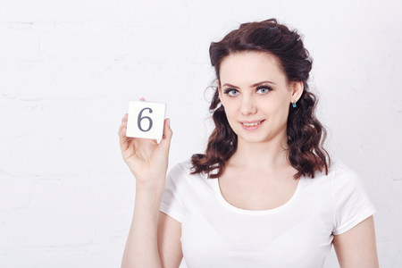 six girl: Young cute girl smiling and holding a number six. Girl dressed in a white t-shirt. Emotional expression.