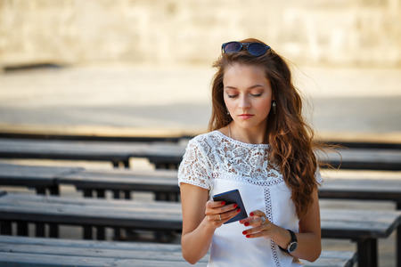 messengers: Lovely girl hipster reading sms on the phone. Communication in social networks. Instant messengers.