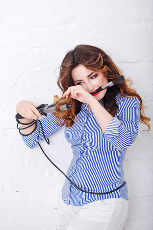 styler: Morning styling. Young attractive girl with curling. Girl in a striped shirt and high heels. Long hair.