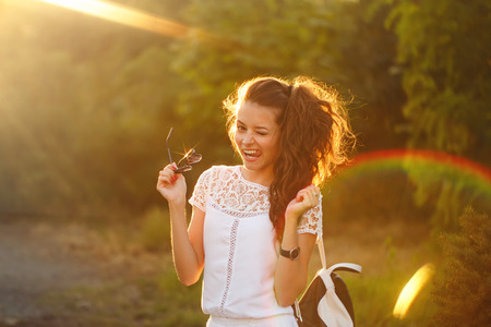pert: Lovely girl hippie walks in the park at sunset. Warm toning. Girl shows tongue and winks. Flirt.
