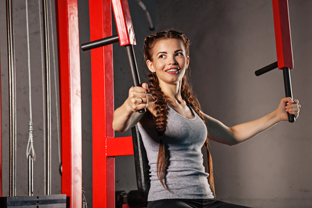 simulator: Young attractive woman athlete exercising on a sports simulator. Sport Club. Fitness club. Healthy lifestyle concept.